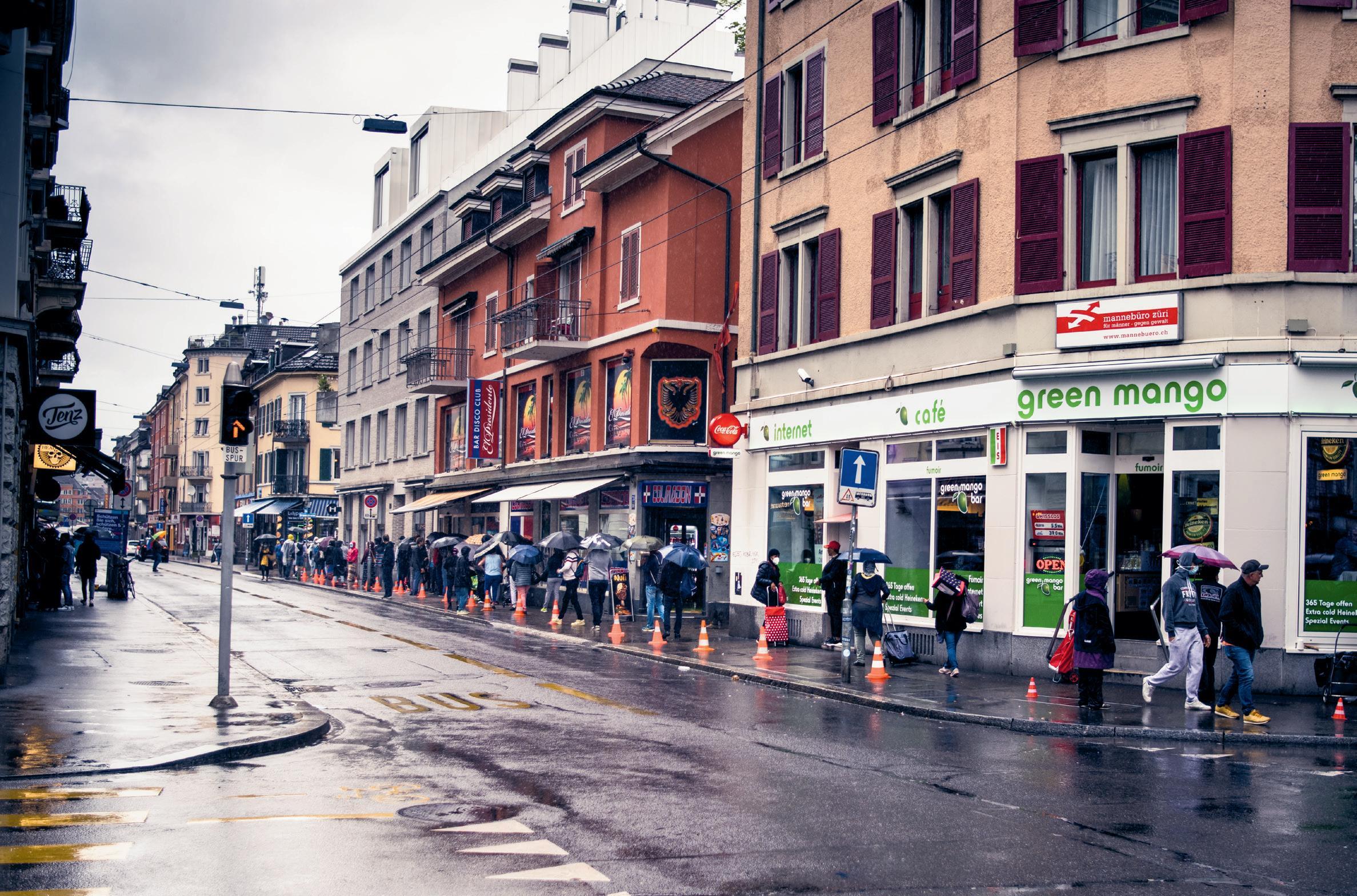 Menschen stehen in Zürich Schlange für Lebensmittel.