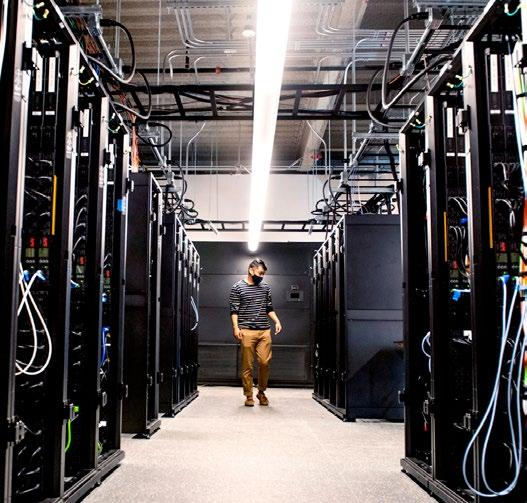 man in wireless data center with many racks of equipment
