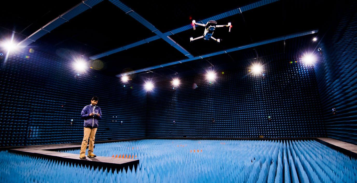 student controlling flying drone in indoor anechoic chamber facility