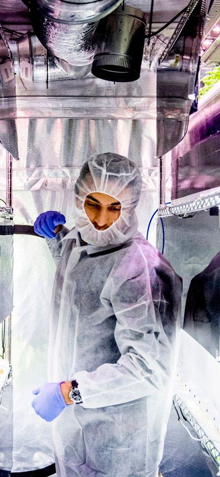 man in clean room white clothes in lab